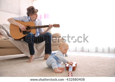Father playing guitar to his son