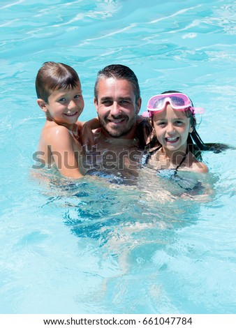 father playing in pool with two child boys and girl