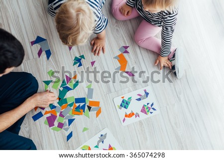 Father playing puzzle with children - stock photo