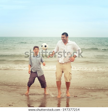 Father playing with a football on the beach while his son watches