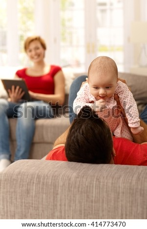 Father playing with baby girl on sofa, mother watching from background. - stock photo