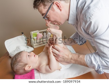 Father playing with cute baby feet after change of diaper and hygiene set for babies on the background - stock photo