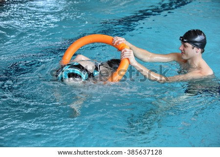 father playing with daughters in swimming pool - healthy lifestyle - stock photo