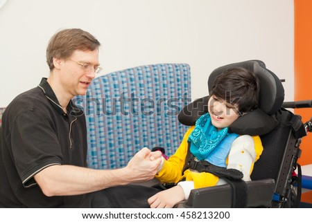 Father playing with disabled biracial son sitting in wheelchair while waiting in doctor's office, laughing together. - stock photo