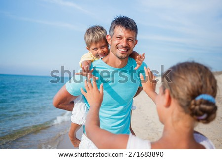 Father playing with his kids at the beach - stock photo