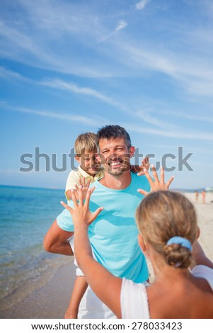 Father playing with his kids at the beach