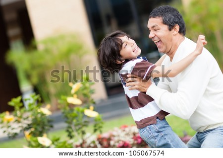Father playing with his son outdoors and having fun - stock photo