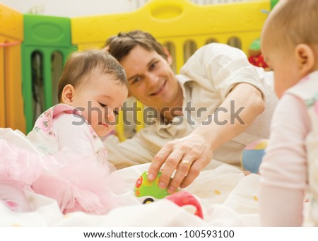Father playing with small babies at home - stock photo