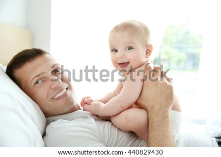 Father playing with smiling baby - stock photo