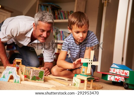 Father playing with son and toys on the floor in a playroom - stock photo