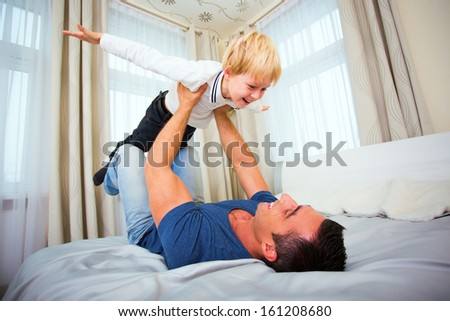 Father playing with son at home.  - stock photo