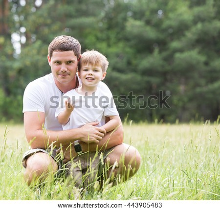 Father playing with son in park