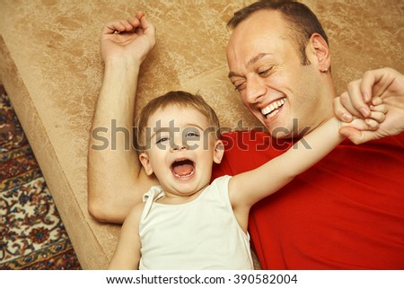 Father Playing With Their Child At Home Dad And Son Having Fun
