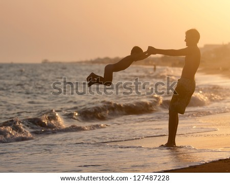 Father plays with his son on the beach at sunset - stock photo