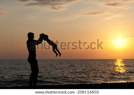 Father plays with son against a sunset