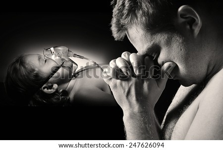 Father prays for the health of seriously ill daughter. MANY OTHER PHOTOS FROM THIS SERIES IN MY PORTFOLIO. - stock photo