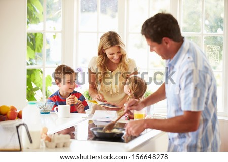 Father Preparing Family Breakfast In Kitchen - stock photo