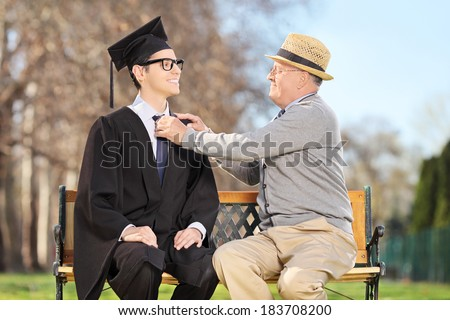 Father preparing his son for graduation seated on wooden bench in park - stock photo