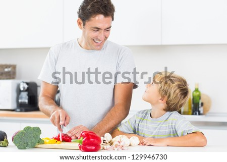 Father preparing vegetables with son in kitchen