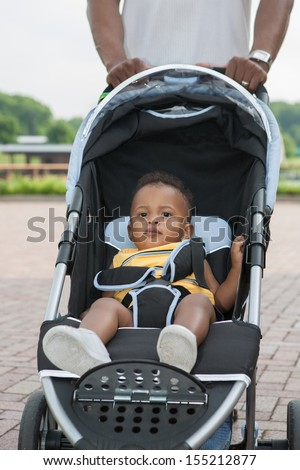 Father Push Little African American Baby Boy in Stroller Outdoor