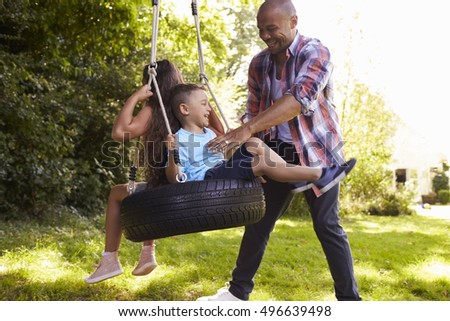 Father Pushing Children On Tire Swing In Garden