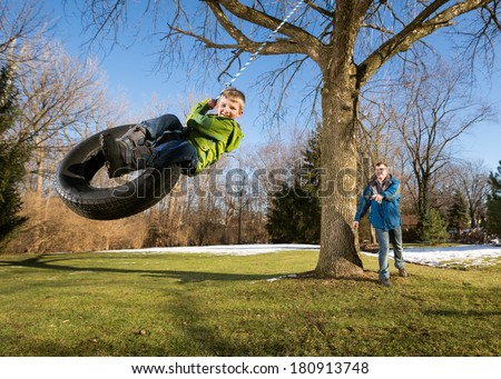 Father Pushing Happy Child on Tire Swing - stock photo