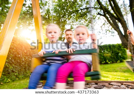 Father pushing his daughters on swing in a park.