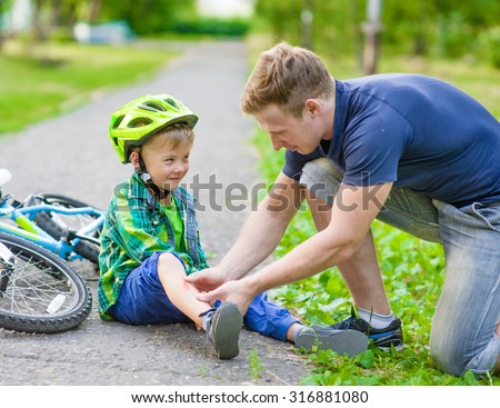 father putting band-aid on young boy's injury who fell off his bicycle. - stock photo