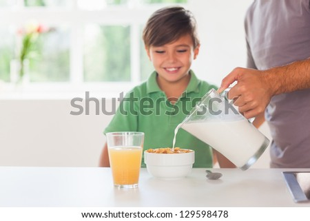 Father putting milk in the cereal of his son in kitchen - stock photo