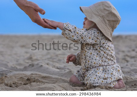 Father reaching his hand to his daughter at the beach - stock photo