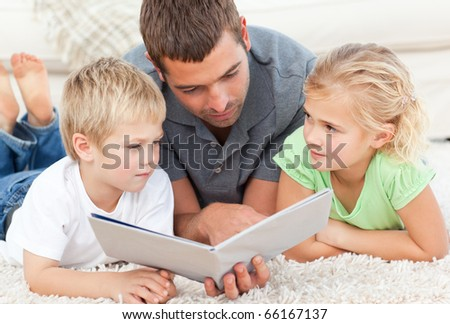 Father reading a book to his children on the floor at home - stock photo