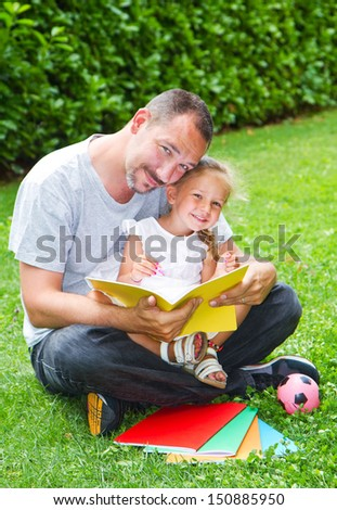 Father reading a book to his daughter while laying on the grass in the garden  - stock photo