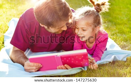 Father reading a book to his daughter while laying outdoor on the grass in the garden during sunset - stock photo