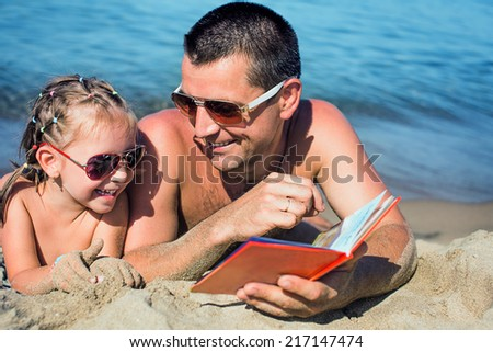 Father reading a book to his daughter while laying outdoor on the seaside  - stock photo