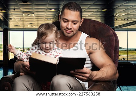 Father reading book to daughter - stock photo