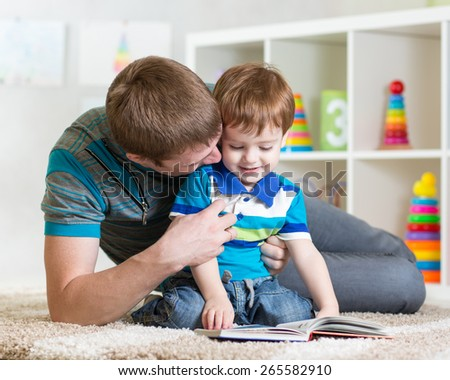 father reading children book to little son - stock photo