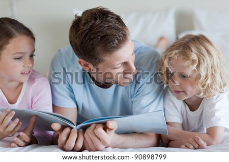 Father reading together with his children - stock photo