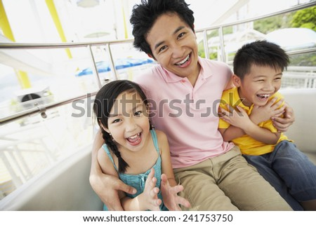 Father Riding Amusement Ride with Daughter and Son - stock photo