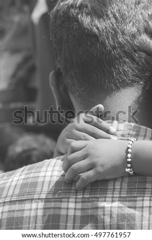 Father's back with daughter's arms around his neck. Vintage effect, black and white photography.