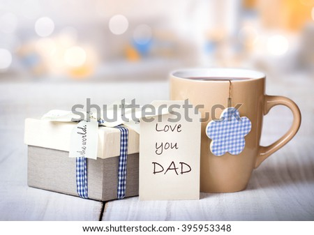 Father's day holiday greeting card.Mug tea coffee and present gift box tag on wooden table blur lights background empty space.Love you dad message. - stock photo