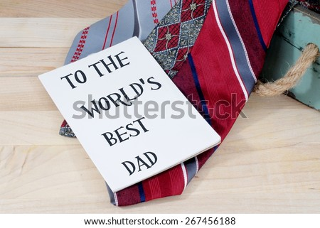 Father's day message on white card on arrangement of red and gray neckties laying on a wooden surface. Removable text on horizontal oriented image. A necktie is a common gift on Father's Day - stock photo