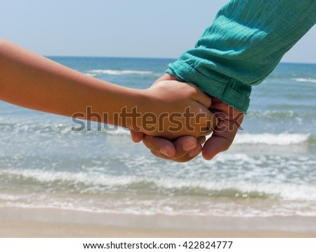 Father's Hand hold by a Daughter hand at the sea, love concept between Father and Daughter.