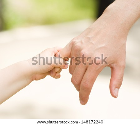 father's hand lead his child son  - stock photo