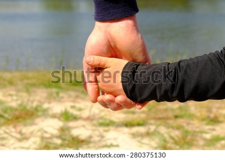 Father's large hand hold hand of a boy. Hands in blue and black shirts.