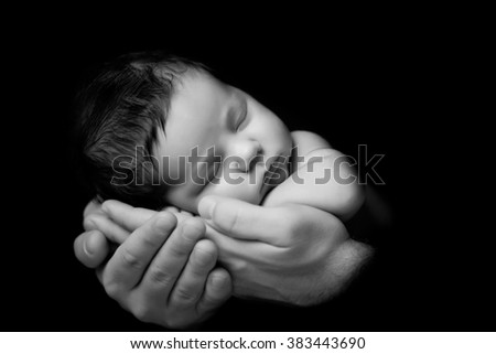 Father's love. Little newborn baby sleeping in Dad 's hands. Close-up on a black background - stock photo