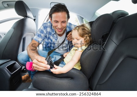 Father securing baby in the car seat in his car - stock photo