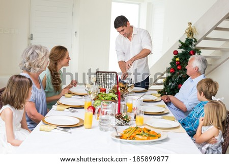Father serving Christmas meal to family at dining table