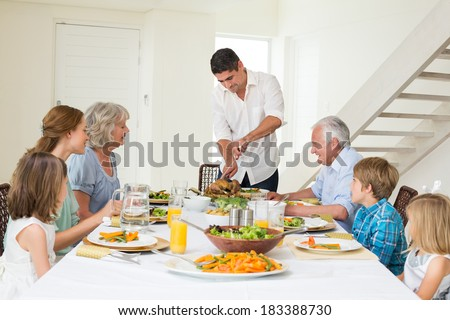 Father serving meal to family at dining table - stock photo