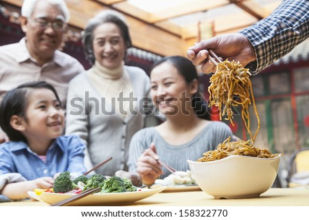Father serving noodles with chopsticks - stock photo