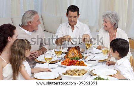 Father serving turkey to his family in a dinner at home